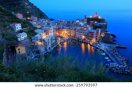 Aerial scenery of beautiful Vernazza at dusk with reflections on peaceful water, an amazing village by the rugged coast in Cinque Terre, Italy - stock photo