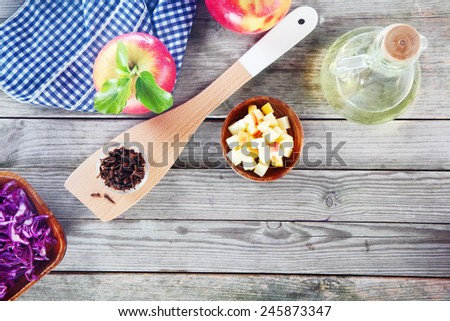 Aerial Shot of Salad Recipe Ingredients on Top of Wooden Table, Emphasizing Apples, Cabbage and Vinegar with Napkin and Wooden Ladle. - stock photo