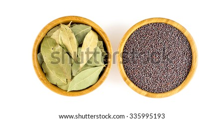 Aerial shot of ��?��� whole dried bay leaves and black mustard seeds in rustic bowls. - stock photo