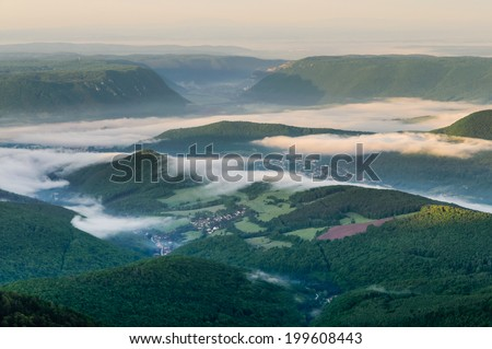 Aerial sunrise view on spectacular green valley of Roznava covered by deep mist in Eastern Slovakia - stock photo