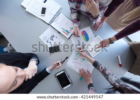 aerial top view  of business people group brainstorming on meeting and businessman presenting ideas and projects on laptop and tablet computer - stock photo