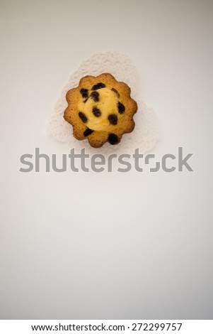 Aerial view delicious cupcake with raisins on white doily closeup  Butter pastry cookie biscuit sponge cake with sultanas on background with natural light - stock photo