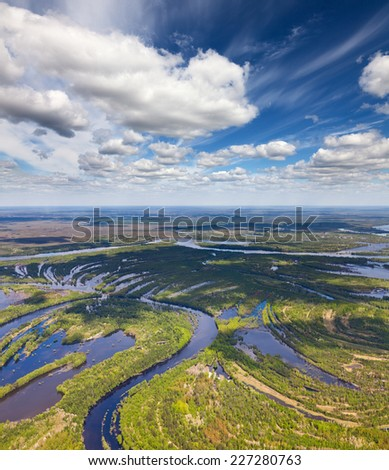 Aerial view flooded forest river lowland under white clouds.  - stock photo