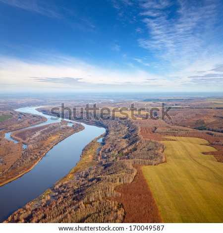 Aerial view forest river in the countryside under clouds near the rural fields where wheat ripened. - stock photo