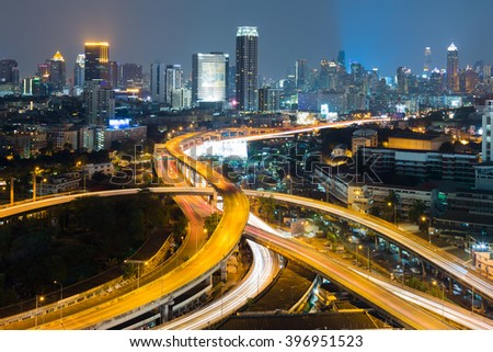 Aerial view interchanged road with city downtown background night view - stock photo
