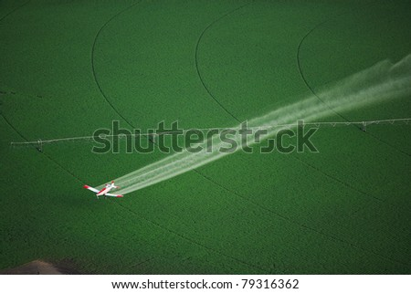 Aerial View of a crop duster spraying a farm field - stock photo