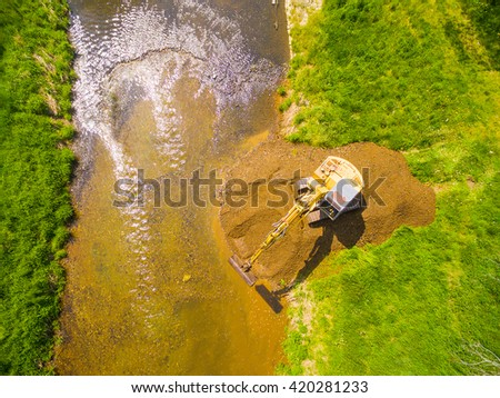 Aerial view of a excavator digging on golden river. Prospecting new locality for mining. Heavy industry and environment. Ecological disaster. Water pollution.  - stock photo