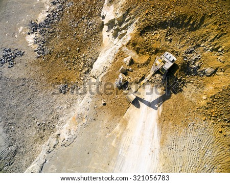 Aerial view of a excavator in the mine. Industrial background from landscape after mining. - stock photo