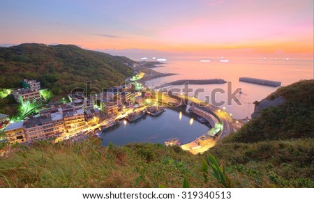 Aerial view of a fishing village at dawn on northern coast of Taipei Taiwan ~ Coastal highway crossing the harbor in a fishing village under dawning sky - stock photo