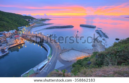 Aerial view of a fishing village at dawn on northern coast of Taipei Taiwan ~ Scenery of a coast highway along beautiful coastline and across the harbor of a fishing village under dramatic rosy sky - stock photo