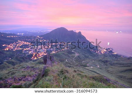 Aerial view of a fishing village by the mountainside on northern coast of Taipei Taiwan ~ Beautiful coastline, coastal highway and a fishing village at dawn with rosy clouds - stock photo