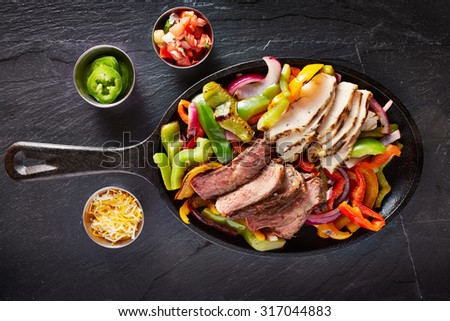 aerial view of a iron skillet filled with steak and chicken mexican fajitas on slate - stock photo