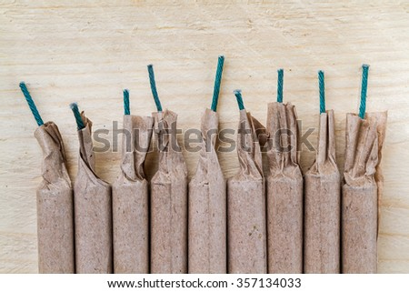 Aerial view of a neat row of nine (9) firecrackers. - stock photo
