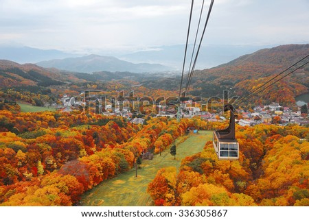 Aerial view of a scenic cable car flying over the beautiful autumn valley of Zao, in Yamagata, Japan ~ Magnificent fall scenery of colorful foliage in Japan - stock photo