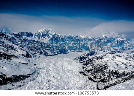 Aerial View of Alaskan Glacier Leading up to Mt. McKinley, Spewing Out Snow and Clouds.  The Great Alaskan Wilderness, Denali National Park, Alaska.  A Beautiful Snowscape of Rock, Snow, and Ice. - stock photo