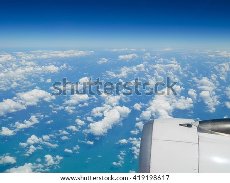 Aerial view of blue ocean and clouds from airplane window - stock photo