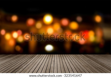 Aerial view of blurred bokeh light in city night with brown wood floor - stock photo