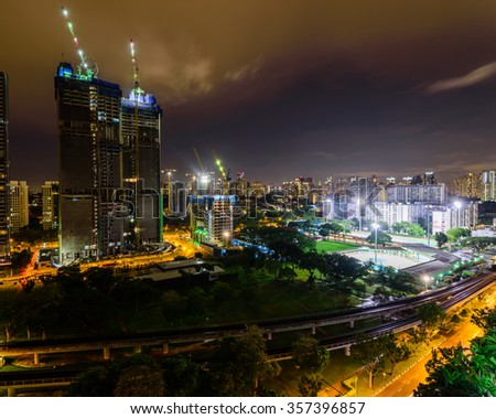 Aerial view of building construction site near the railroad track at Redhill neighborhood in Singapore at night. Urban high rise construction concept - stock photo
