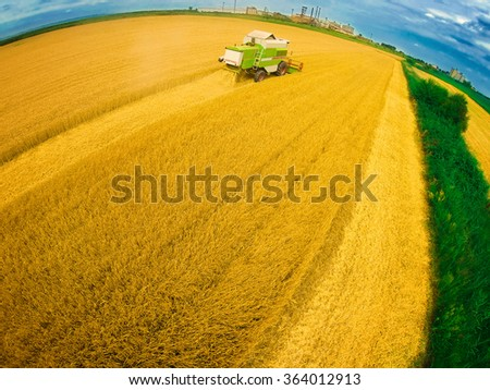 Aerial view of combine on harvest field in Serbia. Wide angle drone shot. - stock photo