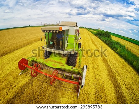 Aerial view of combine on harvest field in Serbia. Wide angle shot. - stock photo