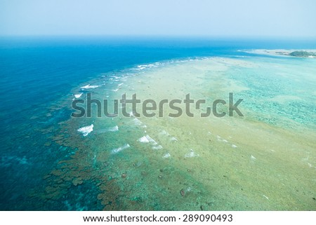 Aerial view of coral reef with clear blue tropical water from a paragliding flight, Amami Oshima Island, Kagoshima, Kyushu, Japan - stock photo
