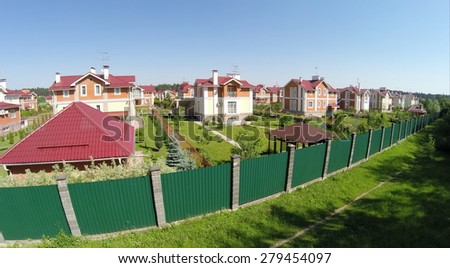 Aerial view of cottage town near forest at sunny summer day. - stock photo