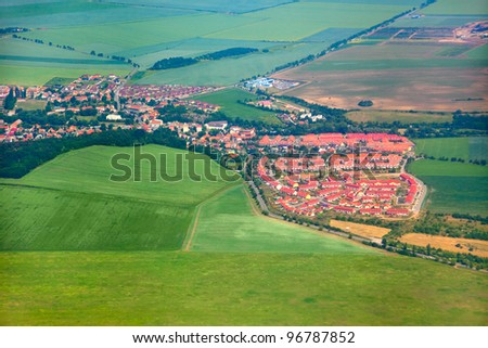 Aerial view of countryside with village and farmland - stock photo
