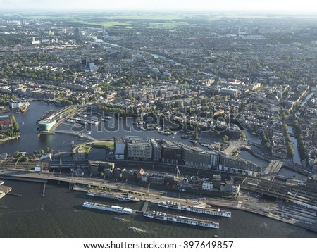 Aerial view of De Ruijterkade in Amsterdam. In the front of the picture four large tour boats and in the back the SCHEEPVAARTMUSEUM and SCIENCE CENTER NEMO MUSEUM. - stock photo