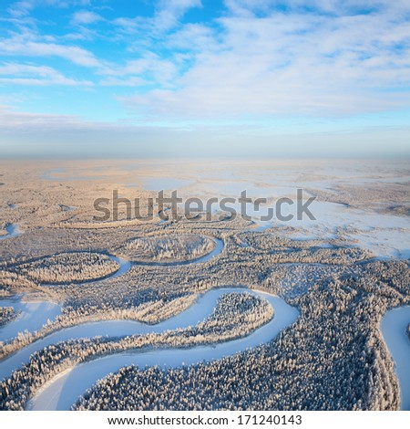 Aerial view of forest river during cold winter day. Magnificent hoarfrost on trees.  A winter forest on rising in a hard frost. - stock photo