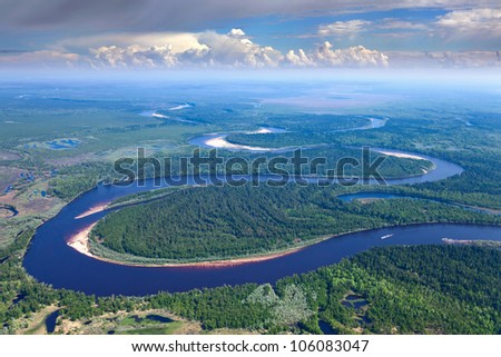 Aerial view of forest the river during summer day on background of great white clouds. The ship with barge moves along the river. - stock photo