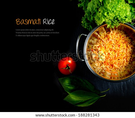 Aerial view of fresh Indian Basmati coloured rice with fresh salad and tomatoes against a dark background. Extended copy space. - stock photo