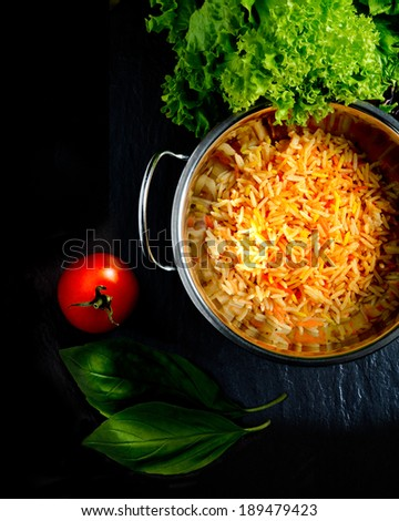 Aerial view of fresh Indian Basmati coloured rice with fresh salad and tomatoes against a dark background. Copy space. - stock photo