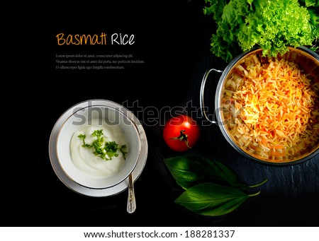 Aerial view of fresh Indian Basmati coloured rice with fresh salad, natural yoghurt and tomatoes against a dark background. Extended copy space. - stock photo
