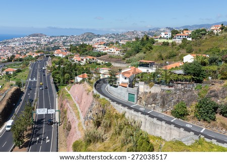 Aerial view of Funchal and highway, build against the mountains of Madeira Island, Portugal - stock photo