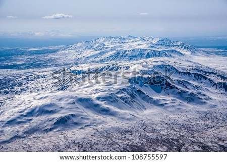 Aerial View of Gentle Sloping Snow Covered Foot Hills in the Great Alaskan Wilderness, Denali National Park, Alaska.  A Beautiful Snowscape of Rock, Snow, and Ice. - stock photo