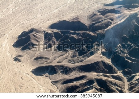 Aerial view of geoglyphs near Nazca - famous Nazca Lines, Peru. On the left side, small Astronaut figure is present. - stock photo