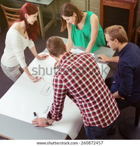 Aerial View of Group of Young Happy Friends Around the Table Making Conceptual Map for their Project Plans. - stock photo