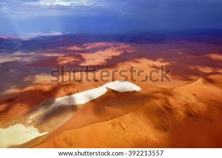 Aerial view of high red dunes and rain on background, located in the Namib Desert, in the Namib-Naukluft National Park of Namibia, Africa - stock photo
