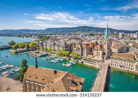 Aerial view of historic Zurich city center with famous Fraumunster Church and river Limmat at Lake Zurich from Grossmunster Church on a sunny day with clouds in summer, Canton of Zurich, Switzerland - stock photo