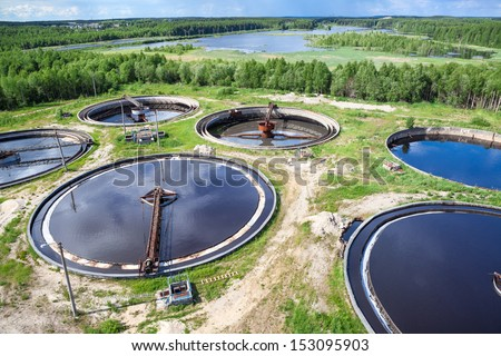 Aerial view of industrial wastewater treatment plant in evergreen forest - stock photo