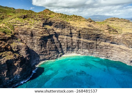 Aerial view of Kauai with its tall sea cliffs along the rugged coastline from a doors off Hughes 500 helicopter tour of the hawaiian Island.  - stock photo