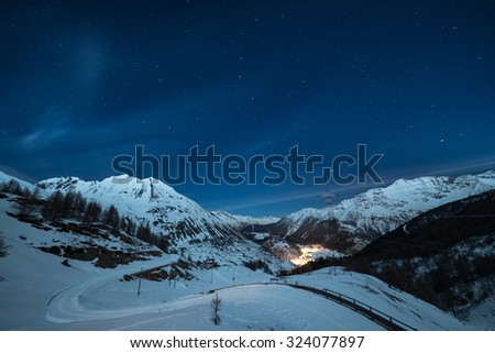 Aerial view of La Thuile village glowing in the night, famous ski resort in Aosta Valley, Italy. wonderful starry sky and majestic mountain landscape illuminated by the moon. - stock photo