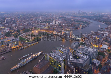 Aerial view of London, UK, at sunset, with the Thames, the Tower Bridge, and the HMS Belfast ship. Taken from The Shard building observation deck. - stock photo