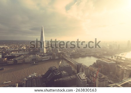 Aerial view of London with The Shard skyscraper and Thames river at sunset with grey clouds in the sky. Vintage filter applied. - stock photo