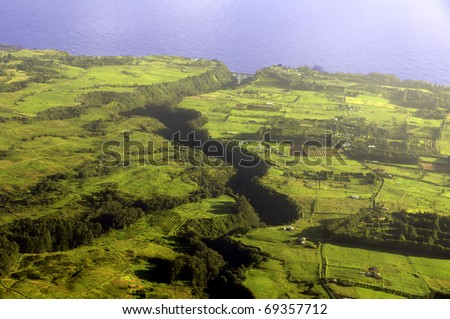 Aerial view of long deep valley cutting across farmland early in the morning, Big Island of Hawaii - stock photo