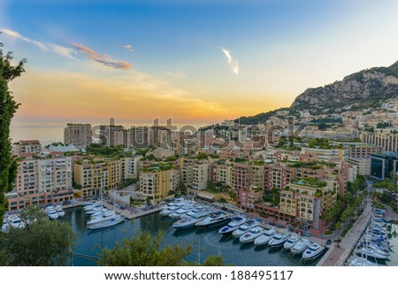 Aerial view of Monaco's harbour with yachts sailing  at sunset - stock photo