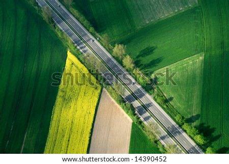Aerial view of motorway between green and yellow flora - stock photo