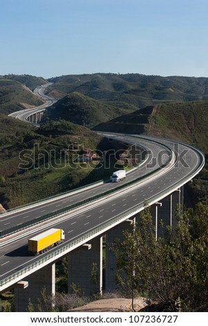 Aerial view of motorway with yellow and white trucks - stock photo
