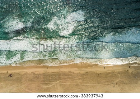 Aerial view of ocean beach. Sand beach and sea view from above. Beach aerial view of ocean water and sand shore. Aerial shot of beach emphasizing the scale of people and nature - stock photo