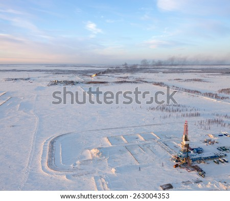 Aerial view of oil rig at an oil field in Western Siberia in the winter day. Gas-jet for gas flaring is located near the rig. - stock photo